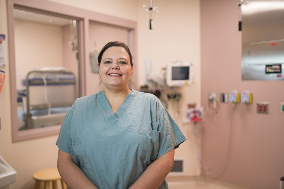 Gillyan Gravelle, registered nurse at Health Sciences North, smiles in a surgical room at Health Sciences North, wearing srubs.