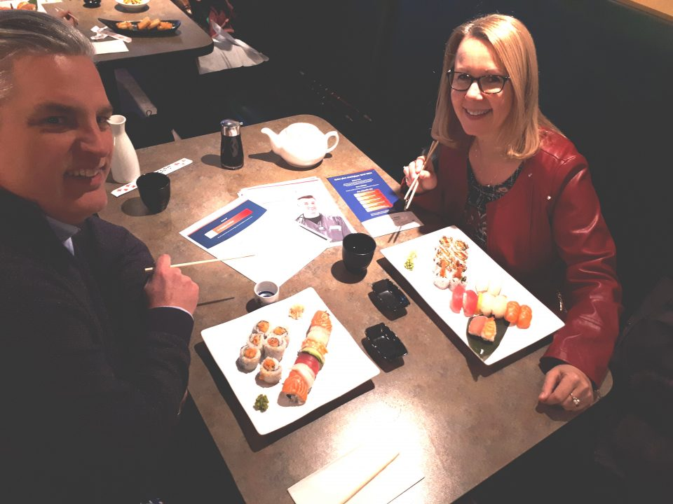 Noel Devost and Anne-Marie Baker Devost eating sushi at a restaurant.